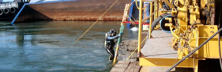 Diver enters water for barge salvage